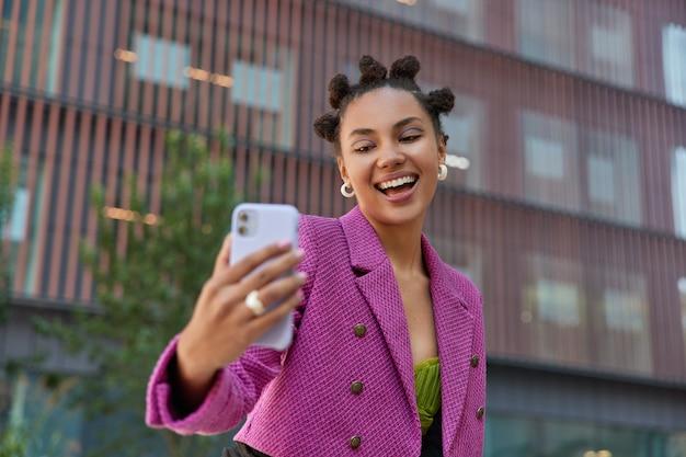 Garota com sorriso cheio de dentes tira selfie em poses de smartphone em um prédio urbano moderno, vestida com uma jaqueta rosa elegante, grava vídeos e fala com seguidores