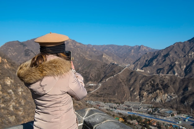 Garota com terno quente espera telefone móvel esperto tirar foto da china grande muralha no inverno em dia ensolarado.