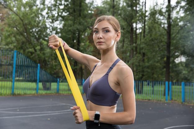 Garota com top esportivo e legging treina com corda elástica amarela no parque