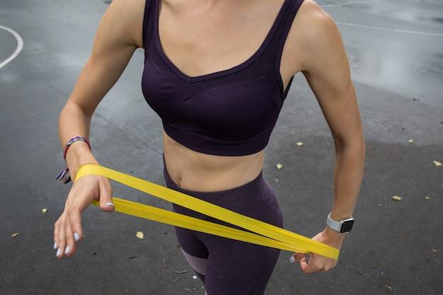 Garota com top esportivo e legging treina com corda elástica amarela