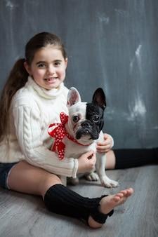 Garota com um cachorro bulldog francês sentado no chão
