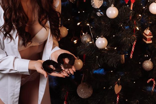 Garota com um corpo sexy em um sutiã branco tem algemas de bdsm nas mãos na árvore de natal para o feriado de ano novo. presente surpresa erótica