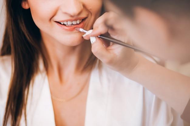 Garota com um jaleco branco desenha os lábios. garota de jaleco branco está sorrindo. menina bonita sorrindo. pinte seus lábios com um pincel.