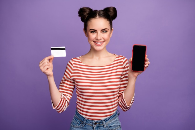 Garota com um penteado moderno usando telefone e cartão de crédito