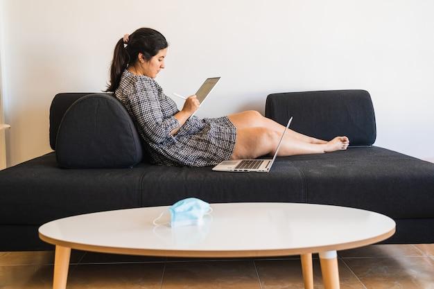 Garota com um vestido descansando em um sofá enquanto estuda online