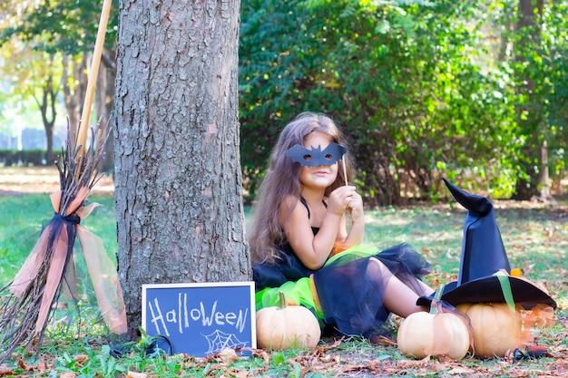 Garota com uma fantasia de bruxa para o feriado de halloween. cartaz com a inscrição: halloween. a garota se senta na grama usando uma máscara de morcego. menina feliz