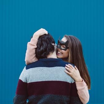 Garota com uma máscara beijando seu jovem.
