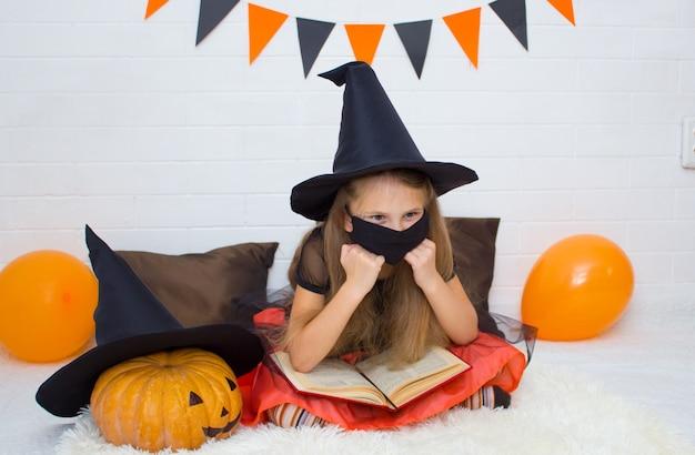 Garota com uma máscara preta e fantasiada de bruxa com um livro de um feiticeiro sentada pensativamente apoiando as mãos
