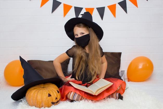 Garota com uma máscara preta e uma fantasia de bruxa com o livro do feiticeiro sentada sorrindo olhando para a câmera