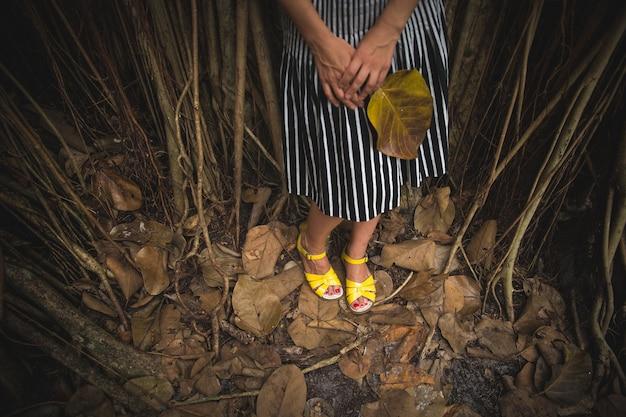 Garota com uma saia listrada e sandálias amarelas parada na floresta tropical escura com uma grande folha