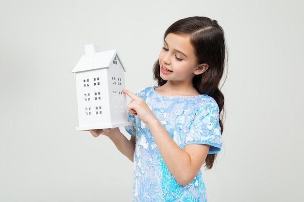Garota com uma simulação de uma casa nas mãos em uma parede branca. a propriedade