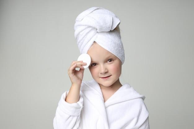 Garota com uma túnica branca e uma toalha na cabeça depois de um banho e lavar o cabelo. cosméticos para crianças e cuidados com a pele, tratamentos de spa.