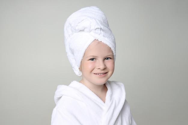 Garota com uma túnica branca e uma toalha na cabeça depois do banho e lavar o cabelo.