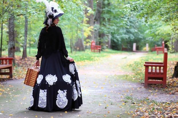 Garota com vestido retrô do século 18 com valise no parque