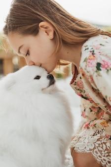 Garota com vista lateral beijando o cachorro