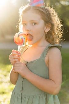 Garota com vista lateral comendo pirulito