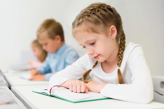 Garota com vista lateral lendo sua lição