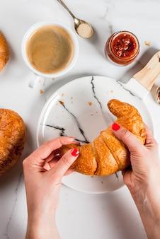 Garota come café da manhã continental caseiro, croissants, café. geléia