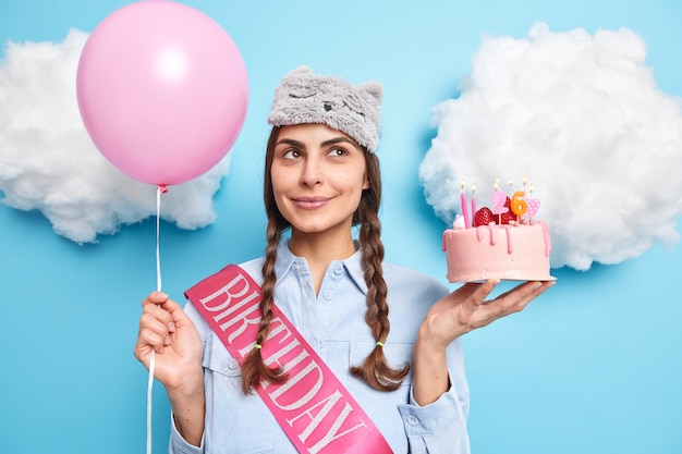 Garota comemora aniversário gosta de atmosfera festiva usa camisa causal vendada poses com bolo delicioso e balão inflado isolado no azul