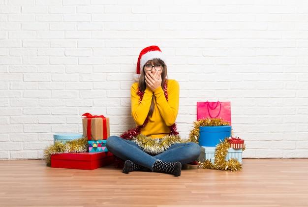 Garota comemorando as férias de natal, cobrindo a boca com as mãos