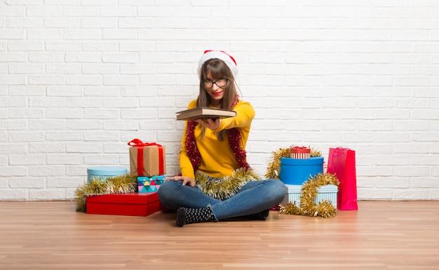 Garota comemorando as férias de natal segurando um livro e dando a alguém