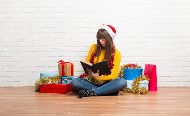 Garota comemorando as férias de natal segurando um livro e desfrutando de leitura