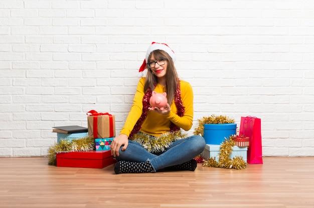 Garota comemorando as férias de natal tomando um cofrinho e feliz porque está cheio