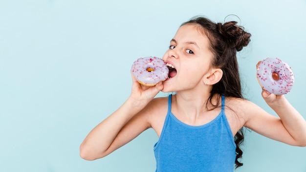 Garota comendo deliciosos donuts com cópia-espaço