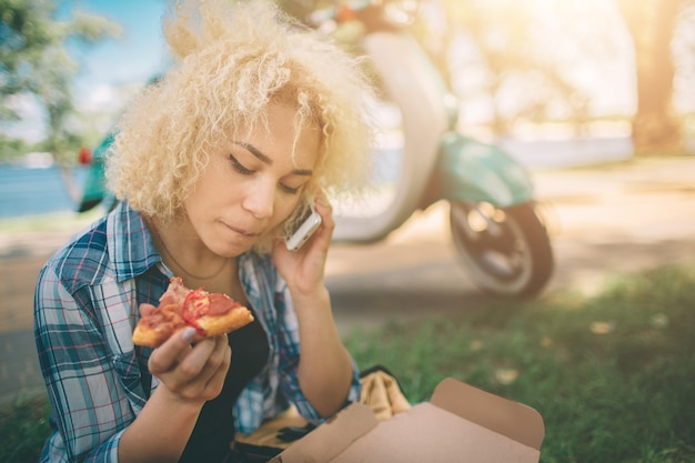 Garota comendo em moto scooter ou ciclomotor. menina comendo em moto scooter ou ciclomotor