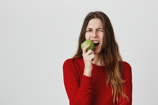 Garota comendo maçã azeda e fazer careta de gosto