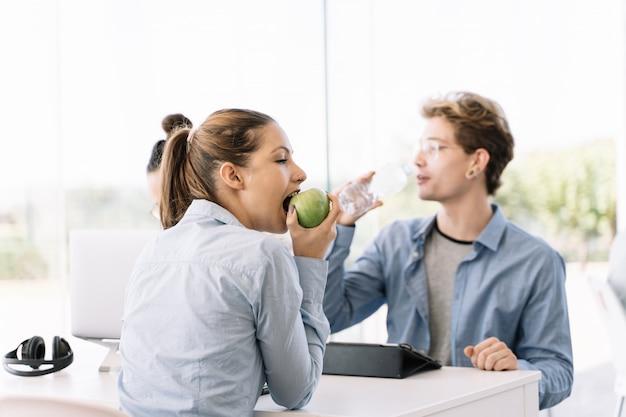 Garota comendo maçã em uma mesa com outras pessoas