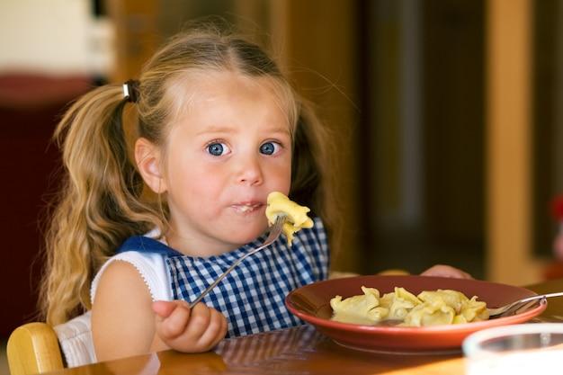 Garota comendo macarrão