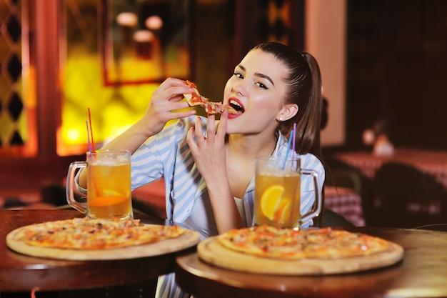 Garota comendo pizza e bebendo cerveja ou um coquetel de citrinos de cerveja no fundo de um bar ou pizzaria.