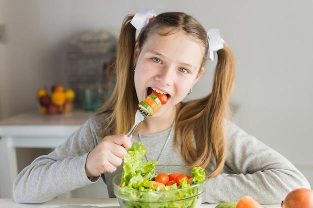 Garota comendo salada de legumes com garfo