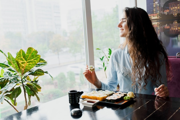 Garota comendo sushi em restaurante japonês
