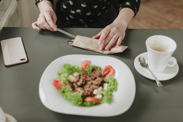 Garota comendo uma salada em um restaurante