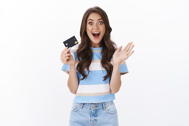 Garota compartilhando uma promoção bancária maravilhosa, sorrindo divertida com olhos esbugalhados, câmera entusiasmada e imaginando, gesticulando com a mão levantada, segurar o cartão de crédito, impressionada com quanto dinheiro de volta, pagando para fazer compras