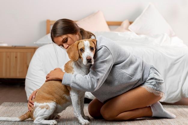 Garota completa abraçando um cachorro