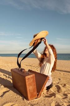 Garota completa com mala e chapéu