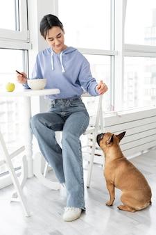 Garota completa comendo perto do cachorro