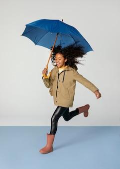 Garota completa correndo com guarda-chuva
