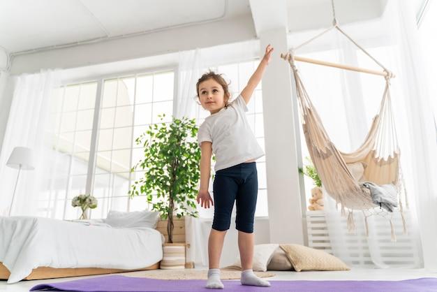 Garota completa em pé no tapete de ioga