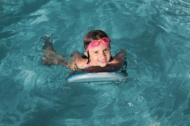 Garota completa nadando com óculos de proteção