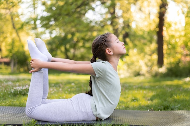 Garota completa se exercitando em um tapete de ioga do lado de fora