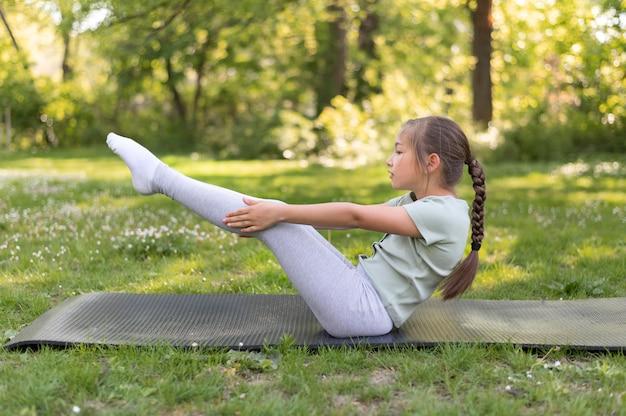 Garota completa se exercitando na esteira de ioga