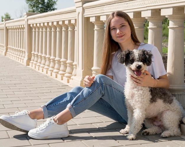 Garota completa sentada com um cachorro fofo