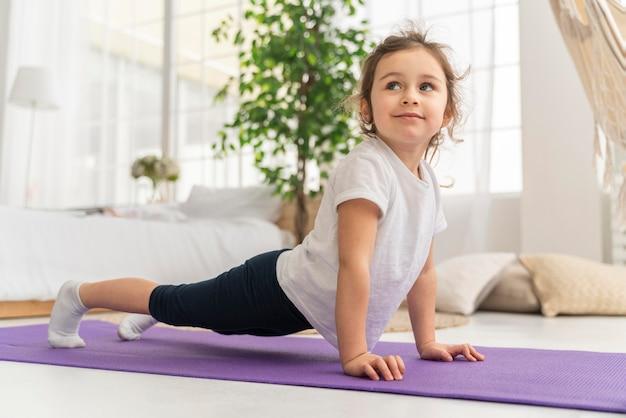 Garota completa treinando em tapete de ioga