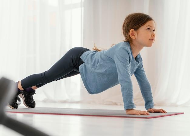 Garota completa treinando no tatame em casa