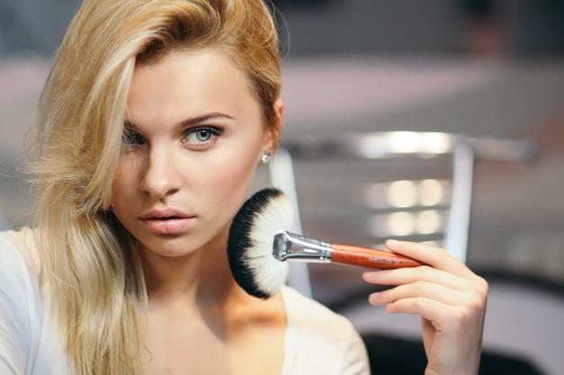 Garota compõem a escova para o conceito de design. maquiagem perfeita. conceito de salão de beleza. maquiagem, cosméticos. jovem modelo caucasiano.
