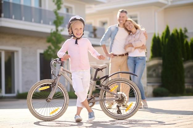 Garota confiante com bicicleta e pais felizes